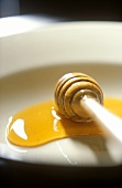 Honey spoon with chestnut honey on a plate