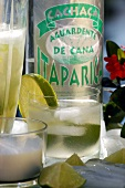 Glass of Caipirinha, bottle of Cachaca Taparica behind