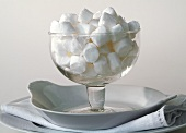 Glass bowl with coconut sweets against white background