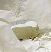Fresh goat's cheese in greaseproof paper, a piece cut off