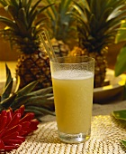 Freshly squeezed pineapple juice in glass with two straws