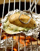 Baked potatoes with cheese filling on grill rack