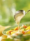 Ladling hollandaise sauce over vegetables