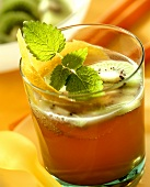 Fruit juice punch garnished with kiwi fruit, lemon peel & mint