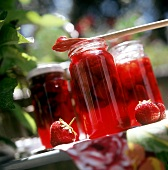Three jars of strawberry jam on a garden table
