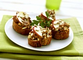 Toasted bread snacks with apple and minced pork topping