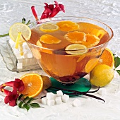 Orange punch in a punch bowl, ingredients beside it