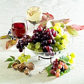 Still life with grapes, red and white wine glass, nuts
