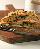 Focaccia mit Käse-Rucola-Füllung auf Küchenbrett