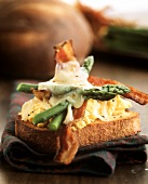 Slice of bread with scrambled egg, bacon, asparagus & cheese