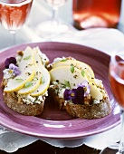 Farmhouse bread topped with Roquefort, pears and pansies