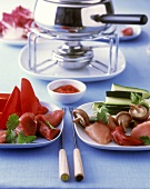Mixed meat fondue, raw ingredients on plates