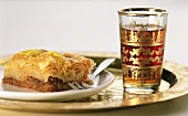 Piece of baklava on a plate and glass of tea