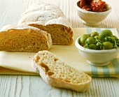 Ciabatta with bowl of green olives on kitchen cloth