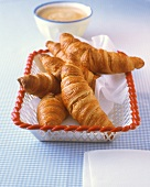 Croissants in bread basket, bowl of white coffee behind