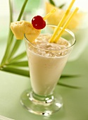 Pina Colada in glass garnished with pineapple, cherry, straws