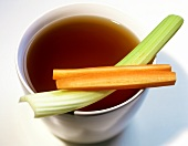 Vegetable stock in a bowl with stick of celery and carrot