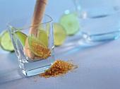 Glass of Caipirinha ingredients (brown sugar, pestle, limes)