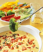 Dipping vegetables into cheese and tomato fondue