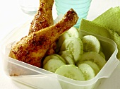 Spicy chicken legs with cucumber slices in plastic container