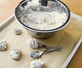 Macaroon mixture in bowl and on baking tray