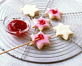 Decorating biscuits with glace icing and jam