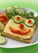Amusing wholemeal toast with Butterkäse cheese & vegetable face