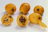 Whole medlars, two half medlars and peeled medlar