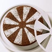 Decorating chocolate cake with icing sugar
