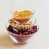 Red lentils, chick-peas and kidney beans in glass bowls