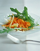 Raw carrot salad with rocket, cheese and pine nuts