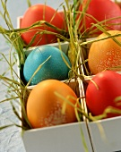Easter eggs in eggcups made of white cardboard & Easter grass