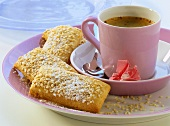 Sesame and ginger sticks with icing sugar; coffee cup