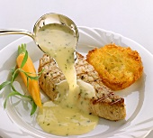 Pouring white wine sauce over grilled salmon steak