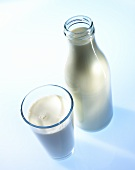 A glass and a bottle of milk