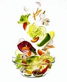 Salatzutaten fallen in eine Schüssel
