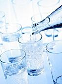 Mineralwasser in Gläser gießen