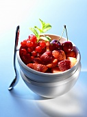 Berry salad with cherries in small bowl