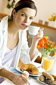 Young woman at breakfast table with coffee