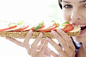 Young woman eating mozzarella and tomato sandwich