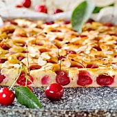 Tray-baked cake with sweet cherries & almonds (a piece cut)