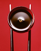 Bowl of soy sauce against red background