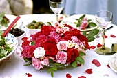 Bowl of roses on table laid for special occasion