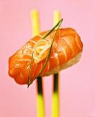 Nigiri-sushi with salmon on chopsticks