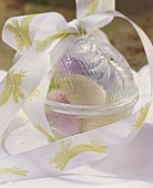 Easter eggs in egg-shaped bowl with gift ribbon