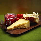 Board with cheese, bread, marinated onions and tomatoes
