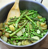 Green asparagus with potatoes and peas in frying pan