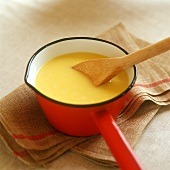Custard with kitchen spoon in a pan