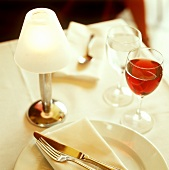Place-setting with red wine and mineral water and a table lamp