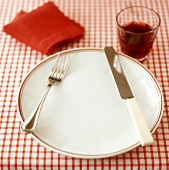 Place-setting for one with red wine on checked tablecloth
